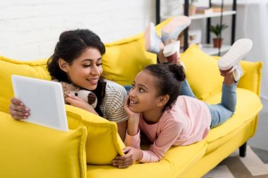 mother and daughter using tablet together on couch