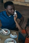 Photo high angle view of careful african american woman cleaning boyfriends face with napkin at table in cafe