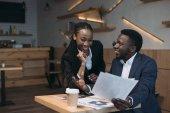 sorridente afroamericano business partner, discutendo il progetto sulla riunione in caffè
