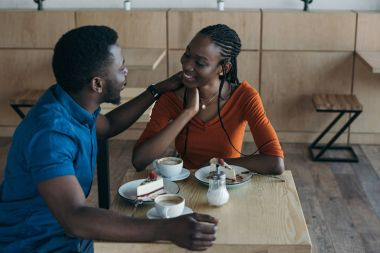 happy african american couple sitting at table with cups of coffee and desserts in cafe