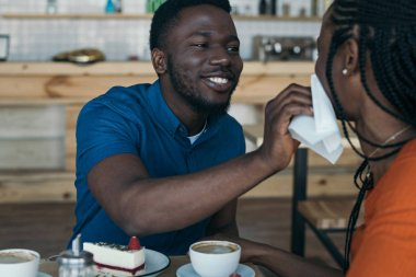careful african american man cleaning girlfriends face with napkin at table in cafe
