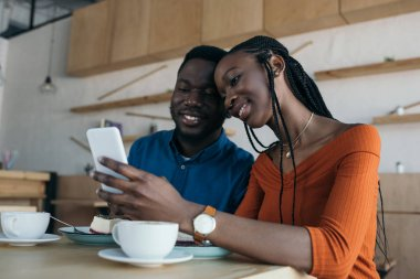 cheerful african american couple using smartphone together in coffee shop