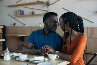 portrait of african american couple looking at each other and holding hands on romantic date in coffee shop