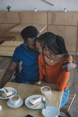 tender african american man hugging girlfriend on romantic date in coffee shop