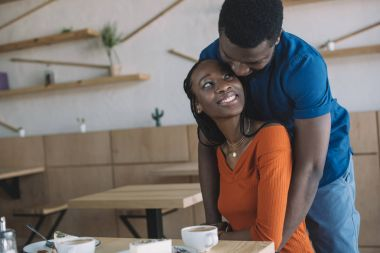 african american man hugging girlfriend on romantic date in coffee shop