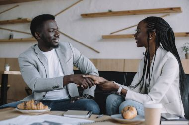 african american business partners shaking hands during business meeting in cafe