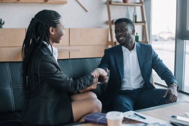 african american business partners shaking hands during meeting in cafe