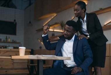 stressed african american businessman with colleague doing massage on meeting in cafe
