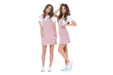 beautiful young twins posing in pink dresses and shirts isolated on white