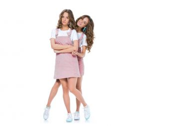 smiling beautiful young twin hugging grimacing sister isolated on white