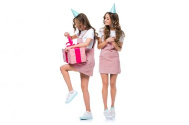 beautiful young twin watching how sister opening present isolated on white