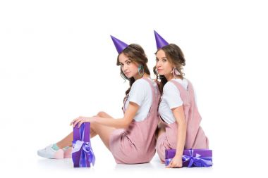 beautiful young twins in birthday caps looking at camera on white