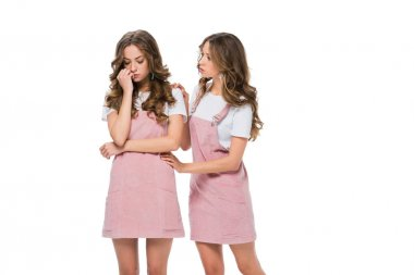 twin comforting upset sister isolated on white