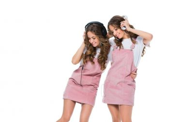 smiling young twins listening music with headphones isolated on white