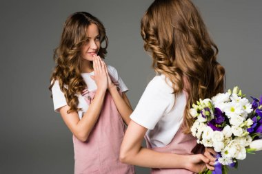twin hiding bouquet from sister to make surprise isolated on grey
