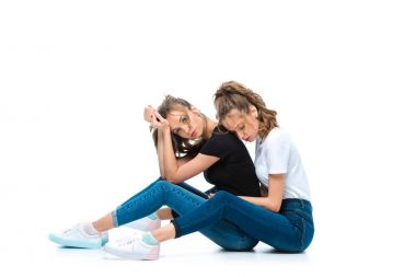 attractive young twins sitting of floor on white