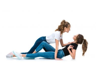 side view of attractive young twin cuddling lying on floor sister on white