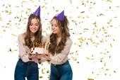 mosolygó ikrek születésnapi caps nézi születésnapi torta alá eső konfetti elszigetelt fehér