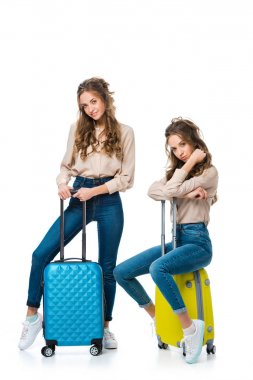 attractive young twins with bags on wheels isolated on white, travel concept