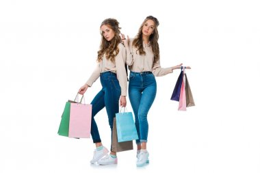 stylish twins in trendy clothes holding shopping bags isolated on white