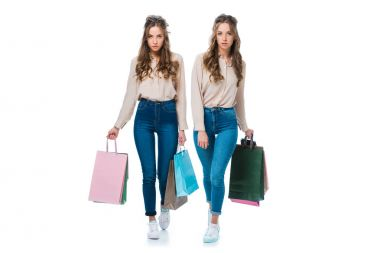 attractive young twins walking with shopping bags isolated on white