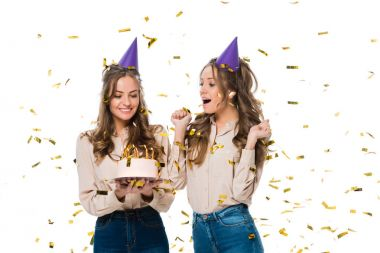 Happy twins in birthday caps looking at birthday cake under falling confetti isolated on white stock vector