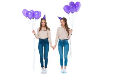 attractive young twins with violet balloons holding hands isolated on white