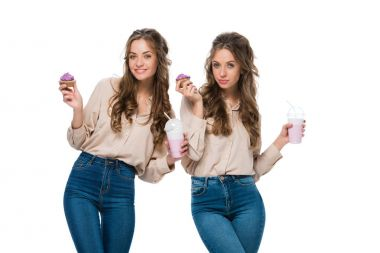 attractive young twins with cupcakes and milkshakes isolated on white