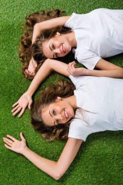 top view of happy attractive young twins lying on green grass and looking at camera