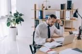 Fotografie focused lawyer in eyeglasses doing paperwork at workplace in office
