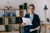 portrait of female lawyer in suit with documents in hands at workplace in office