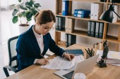 Fotografie side view of female lawyer doing paperwork at workplace with laptop in office