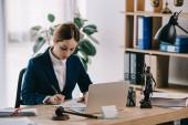 Fotografia avvocato femminile in vestito sul posto di lavoro con computer portatile, martelletto e femida in ufficio
