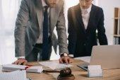 Teilansicht von Rechtsanwälten in Anzügen, die gemeinsam an einem Projekt am Arbeitsplatz mit Hammer und Laptop im Büro arbeiten