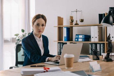 portrait of female lawyer in suit looking at camera at workplace in office