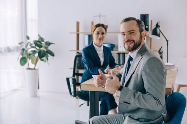 selective focus of smiling businessman showing thumbs up and colleague behind at workplace in office