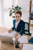 Fotografie focused businesswoman in suit doing paperwork at workplace in office