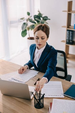 focused businesswoman in suit doing paperwork at workplace in office