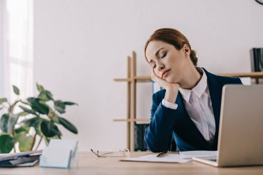 portrait of tired businesswoman sleeping at workplace in office