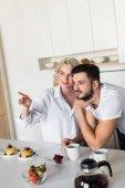 lächelnd junges Paar wegschauen während zusammen frühstücken