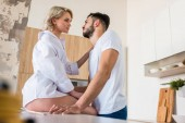 Fotografie Seitenansicht des sinnlichen junges Paar sahen einander in Küche am Morgen