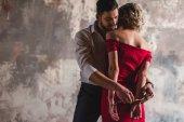 pohledný mladý muž nasadil pouta svůdné ženy v červených šatech