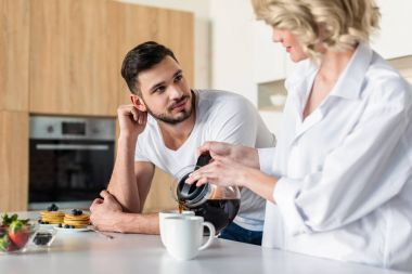 young woman pouring coffee and looking at handsome boyfriend at morning in kitchen