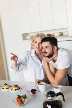 smiling young couple looking away while having breakfast together