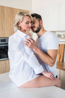 seductive happy young couple hugging in kitchen at morning