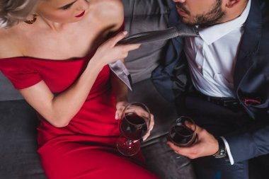 cropped shot of fashionable couple drinking wine, woman holding necktie of handsome boyfriend