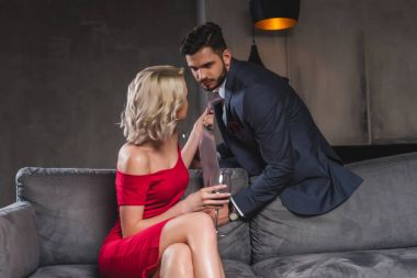 Seductive stylish couple looking at each other, woman drinking wine and holding necktie of boyfriend stock vector