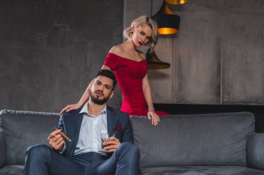 man in suit holding cigar and glass of whisky while spending time with sexy girl in red dress