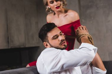 sensual young woman in red dress tying hands of handsome boyfriend with rope