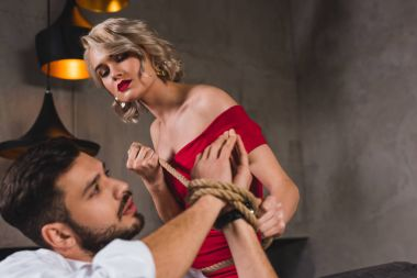 seductive young woman in evening gown tying hands of handsome boyfriend with rope